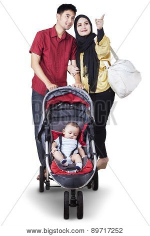 Two Parents With Baby In The Stroller