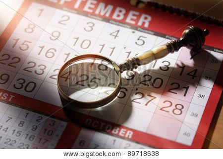 Calendar planning magnifying glass resting on an important date concept for deadline business appointment or meeting