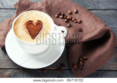 Cup of cappuccino with heart of cocoa on wooden table