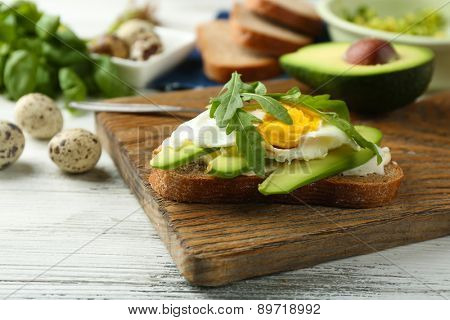 Tasty sandwich with egg, avocado and arugula on wooden background