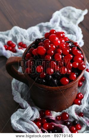 Cup of juicy berries on wooden table with scarf