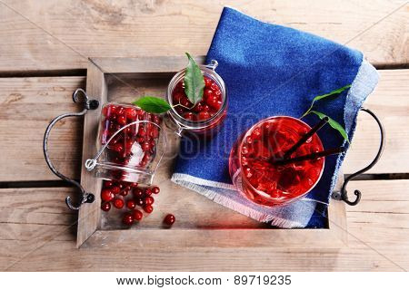 Compote with red currant on tray on wooden background