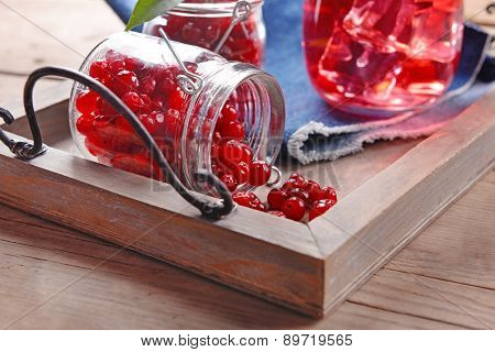 Red currant in glass jars on wooden tray, closeup