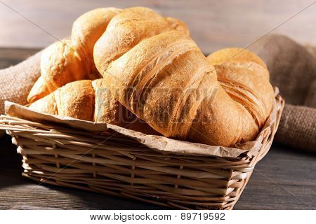 Delicious croissants in wicker basket on table close-up