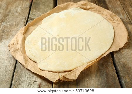 Rolled dough on paper on wooden background