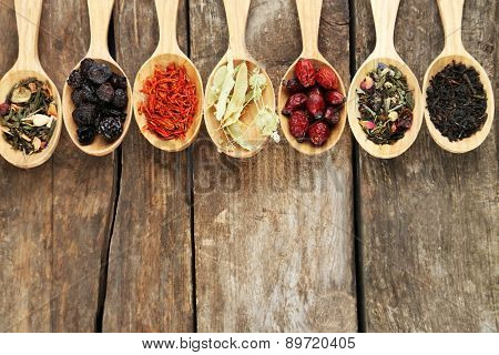 Collection of tea and natural additives in wooden spoons, on old wooden table