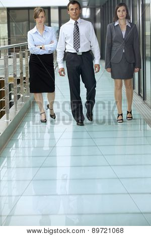 Portrait of business people walking on corridor at office