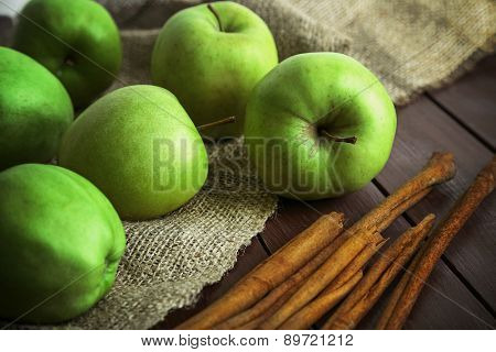 Green apples with cinnamon sticks on wooden table with sackcloth, closeup