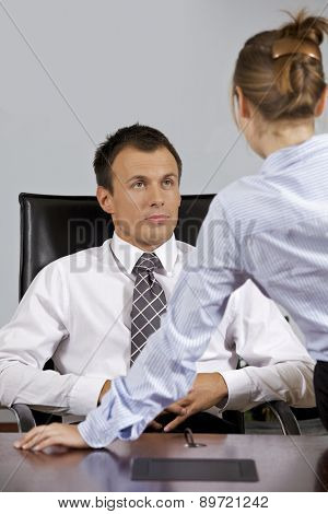 Businessman and businesswoman looking at each other in office