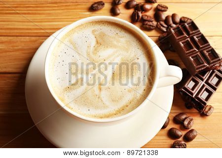Cup of coffee latte art with grain and chocolate on wooden table, closeup