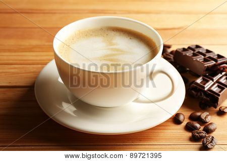 Cup of coffee latte art with grain and chocolate on wooden background