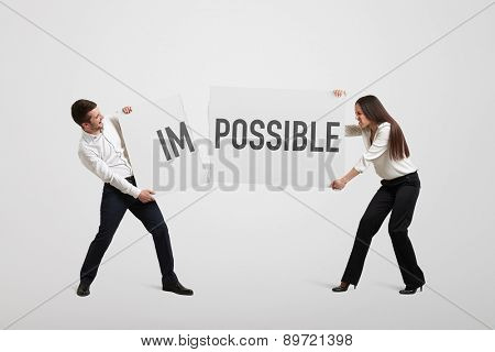 businessman and businesswoman tearing banner with word impossible for possible over light grey background