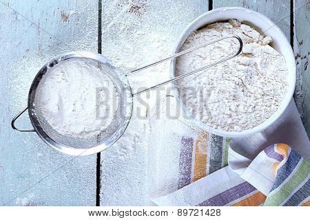 Sifting flour through sieve on wooden table, top view