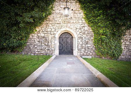 Small Door At Stone Wall Of Old Castle.