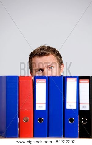 Portrait of businessman sitting behind files at office