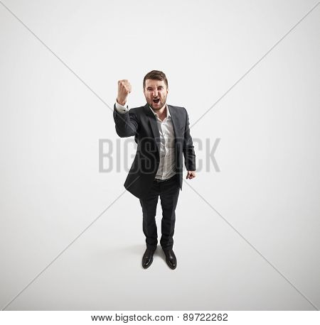 view from above of screaming man showing fist and looking at camera over light grey background