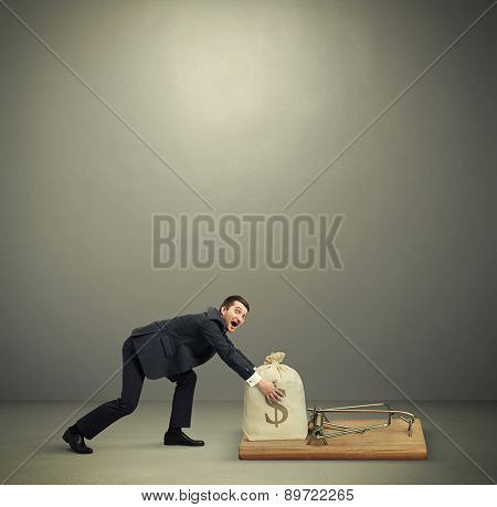 amazed man in formal wear reaching his hands to take bag with money in big mousetrap over dark grey background with empty copyspace overhead