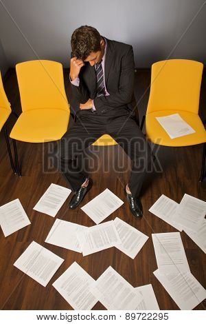 Businessman sitting with head in hands, documents scattered on floor