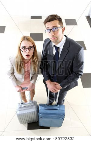 Funny couple with suitcases on light background