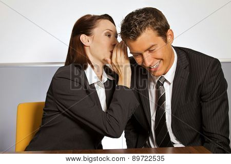 Businesswoman whispering in businessman's ear at office