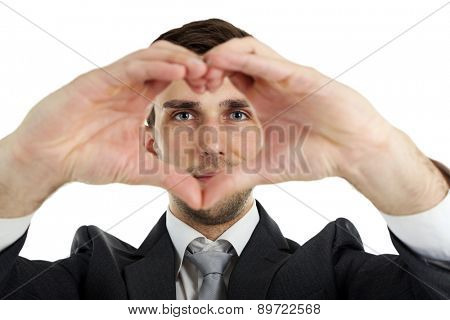 Smiling attractive young man makes the heart using fingers