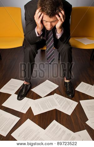 Businessman sitting with head in hands looking at documents scattered on floor