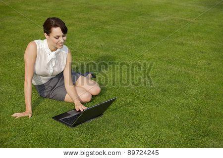 Businesswoman using laptop at park