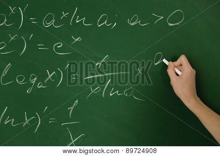 Female hand writing formulas on blackboard with chalk, close up