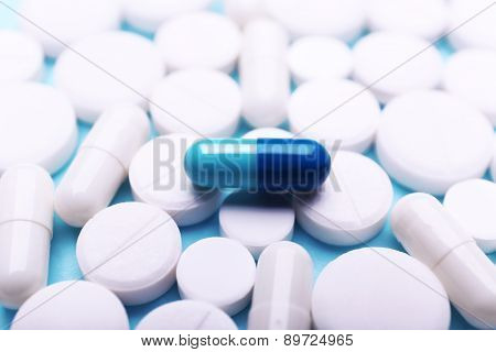 White pills and blue one, closeup