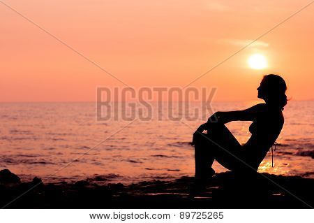 Woman silhouette sitting on sea background back lit