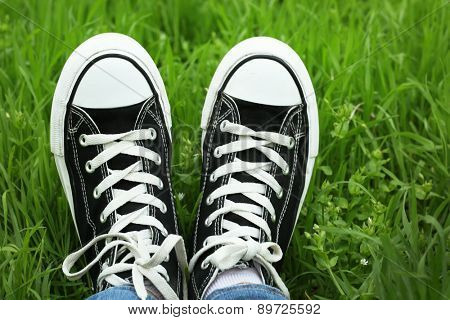 Female feet in gumshoes on green grass background