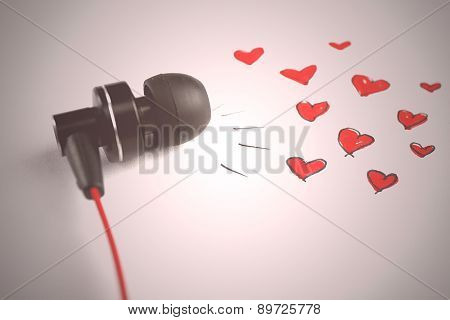 Earphones on white sheet of paper with small hearts, closeup