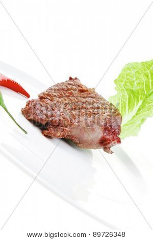 meat food : roast beef steak garnished with green lettuce and red chili hot pepper on white plate isolated over white background