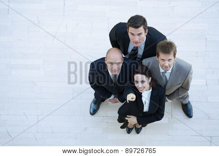 Businesswoman and men looking up and smiling