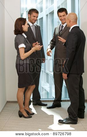 Portrait of young caucasian business people talking in office