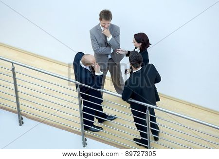 Businessmen and woman standing together by railing