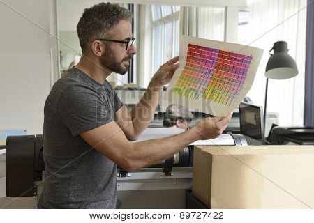 Printing industry: Graphic designer checks the color with color swatch.