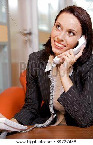 Businesswoman conversing on landline phone