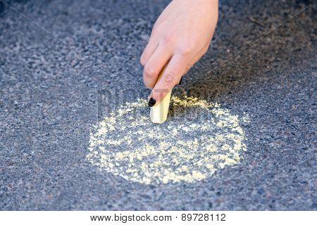 Girl drawing with chalk on asphalt