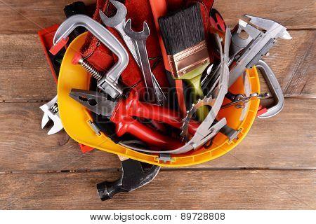 Construction tools in helmet on wooden background