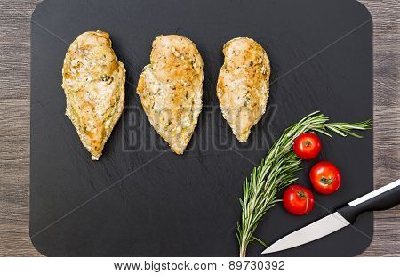 Chicken breast on cutting board.