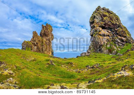 The picturesque ancient rocks covered with a green and yellow moss. Magnificent Iceland. Northern sea coast