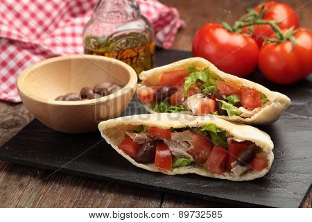 Pita bread stuffed with turkey meat, tomato, kalamata olives, and lettuce