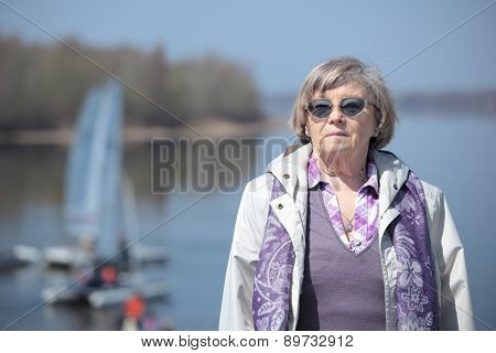 Senior woman against a river in springtime