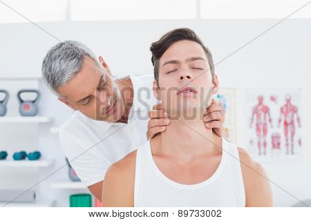Doctor massaging a young man neck in medical office