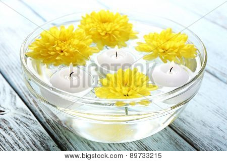 Bowl of spa water with flowers and candles on wooden table, closeup