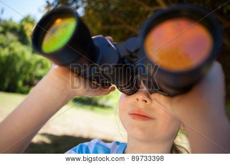 Cute little girl looking through binoculars on a sunny day