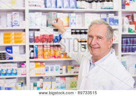 Smiling pharmacist taking medicine from shelf in the pharmacy