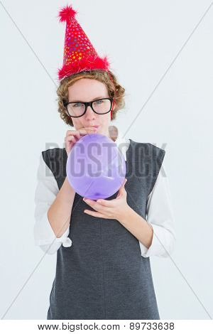 Geeky hipster blowing up balloon on white background