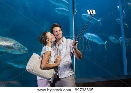 Happy couple using selfie stick at the aquarium